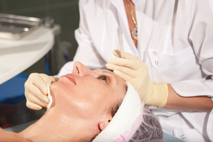 Woman having jet peeling facial treatment